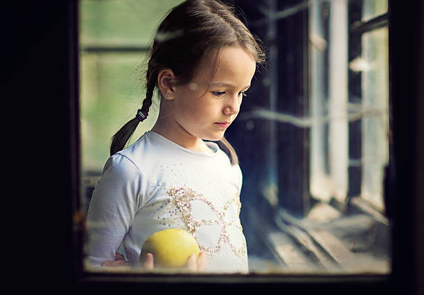 Portrait of the youang girl with apple standing in the old house.
